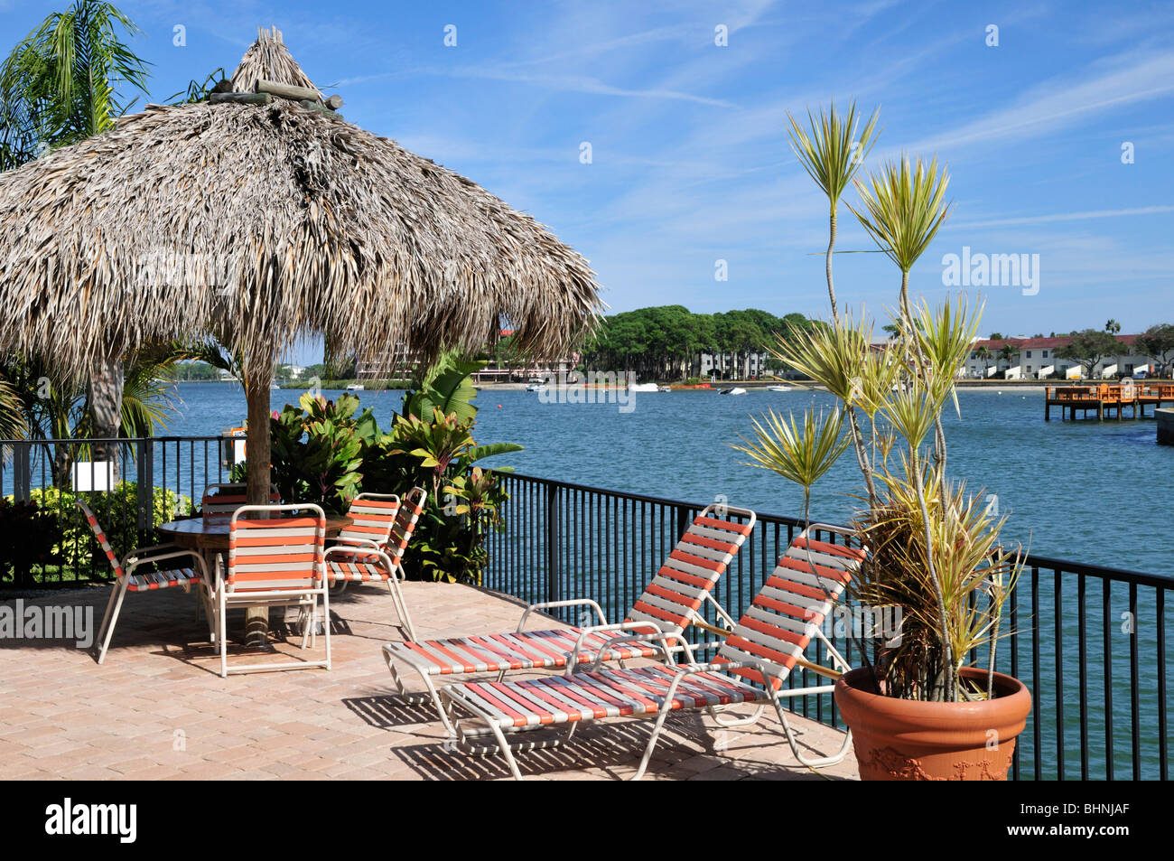 Chaise lounges, tiki roof, potted plants with a view of a Florida waterway - Stock Image