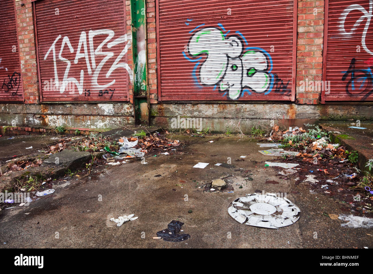 Graffiti on garage doors in urban street scene littered with dumped rubbish. Liverpool, England, UK, Britain. - Stock Image
