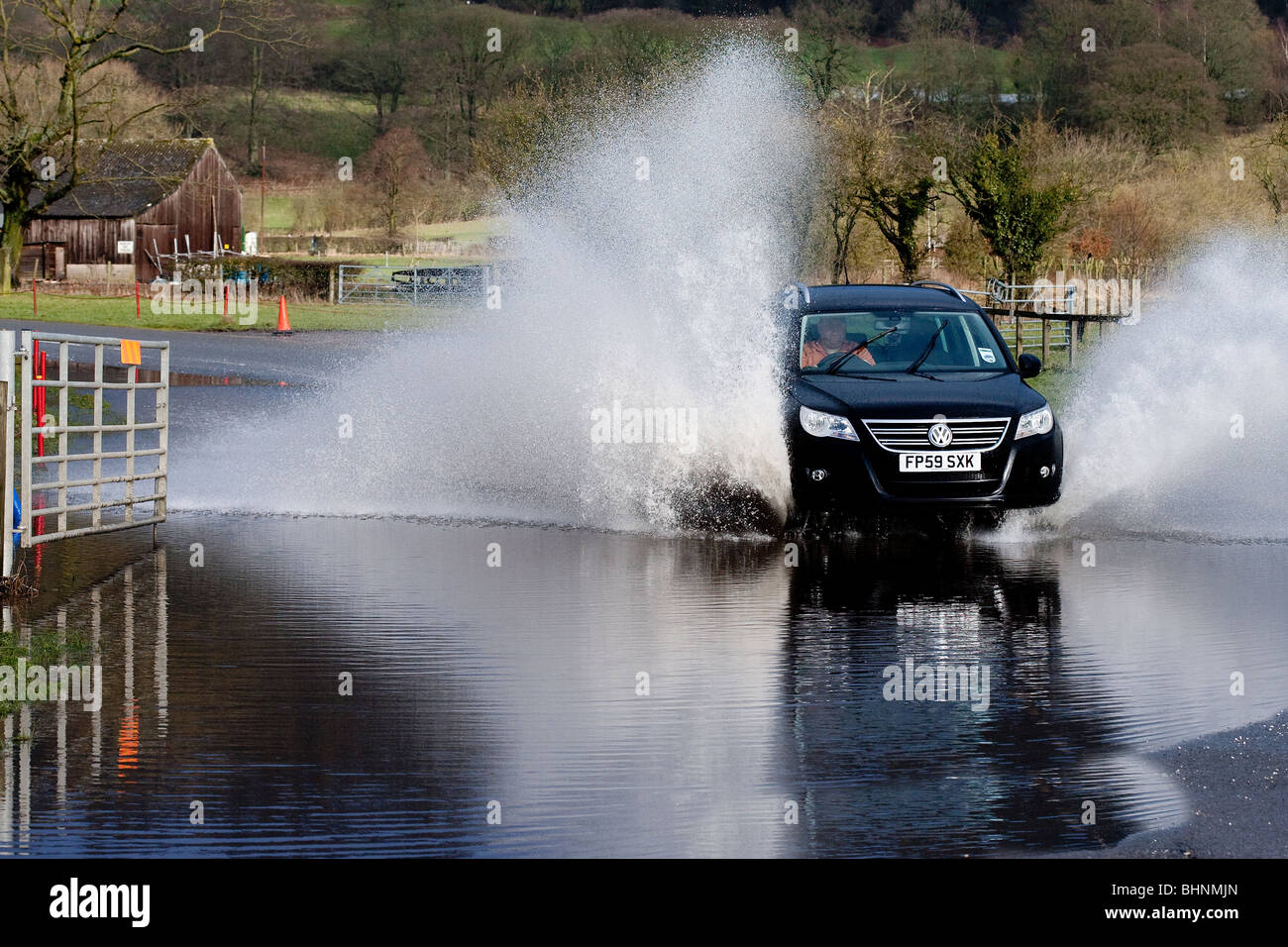 VW Motor Vehicle travelling at speed through flooded grounds in Derbyshire near Bakewell - Stock Image
