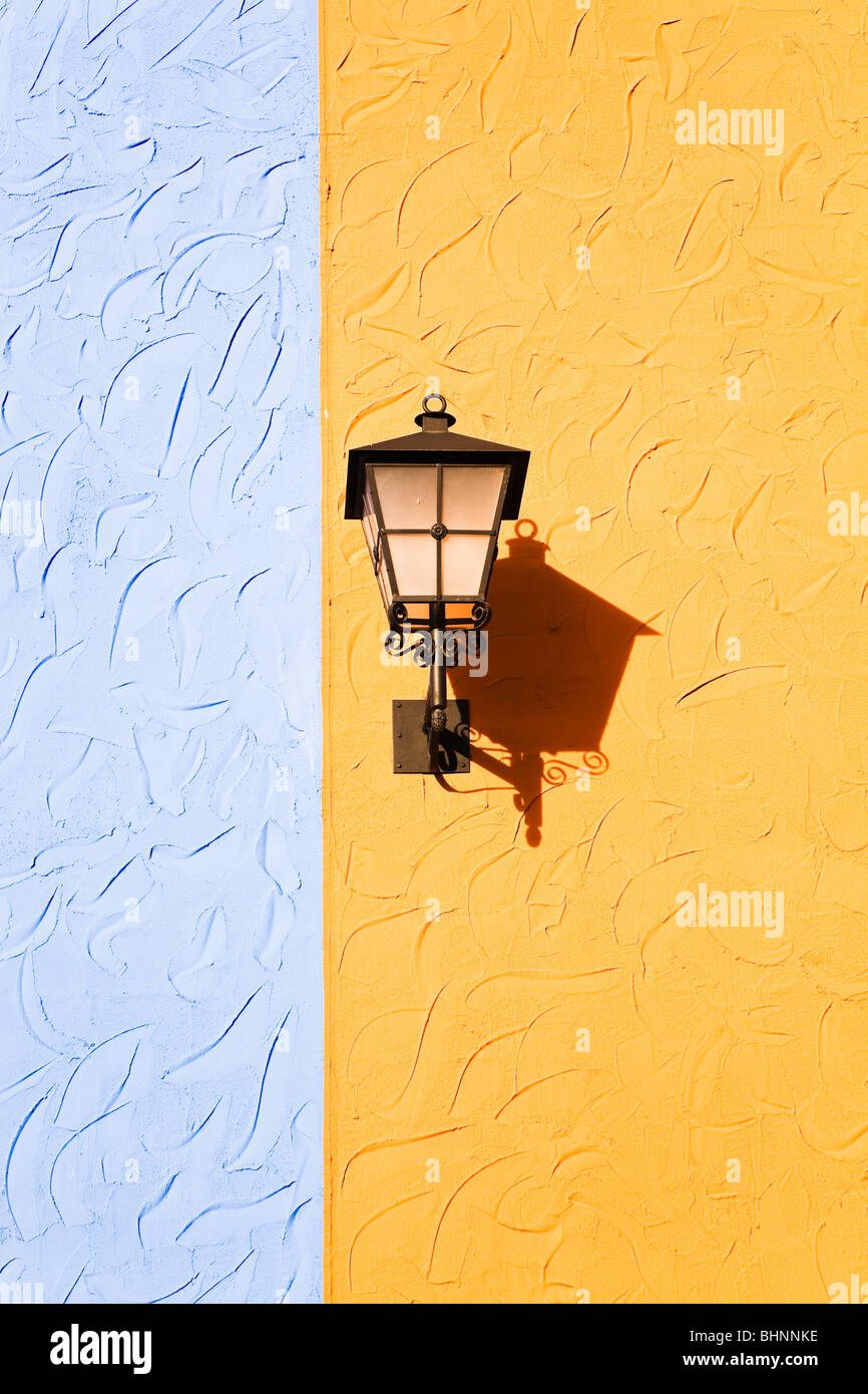 Street lamp against coloured walls at Plaza Mayor shopping centre, Malaga, Costa del Sol, Spain. - Stock Image