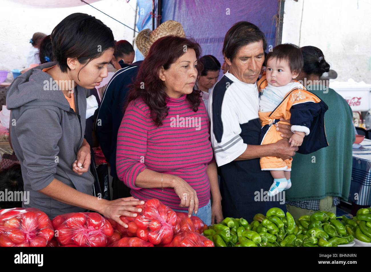 handsome Mexican family with chubby baby boy & pretty teen daughter consider vegetable purchase at Ocotlan Market - Stock Image