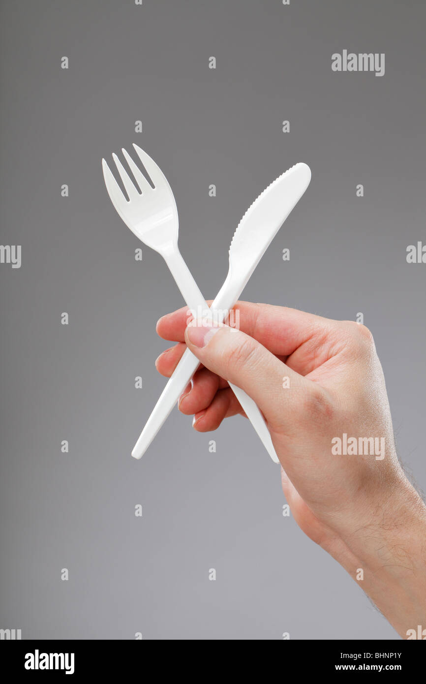 Hand holding white disposable plastic fork and knife - Stock Image
