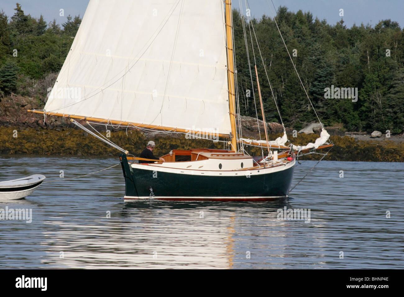 Double-Ended Sloop NETTIE sails away after weighing anchor in Pulpit Harbor - Stock Image