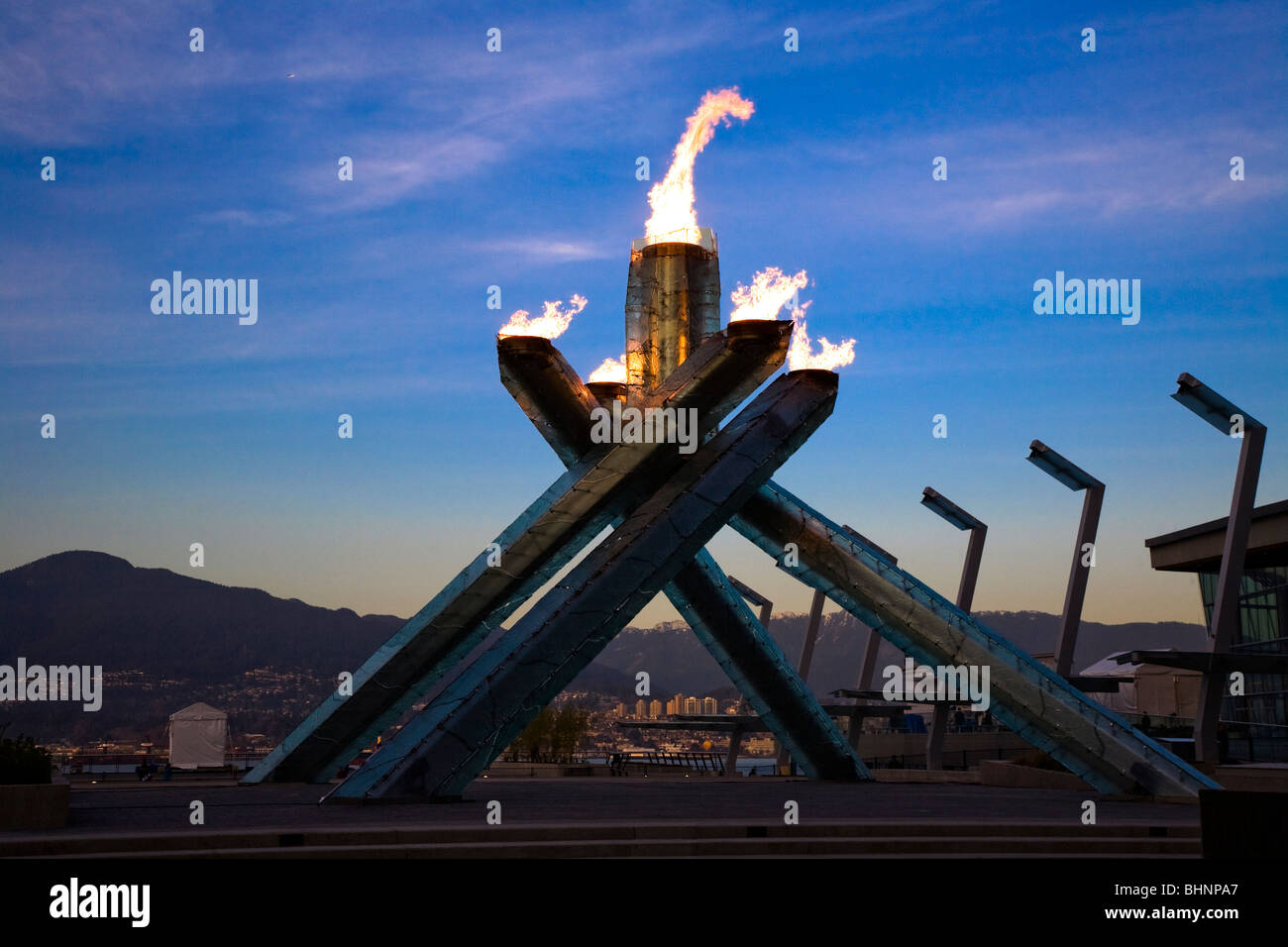 The Olympic Cauldron burns against a darkening sky at the Vancouver 2010 Winter Olympics - Stock Image