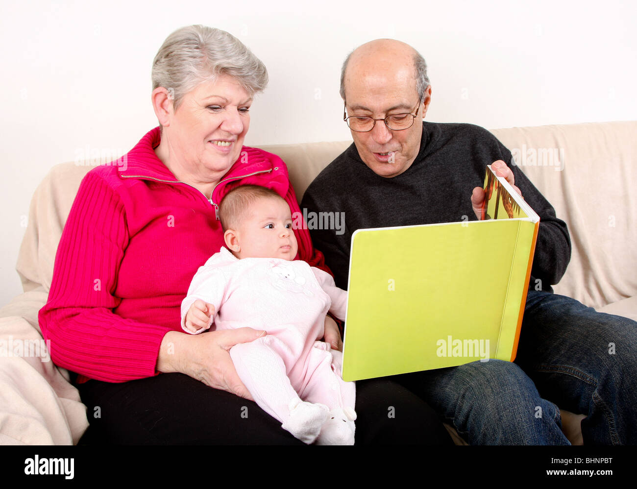family sitting together on couch reading book to baby grandfather