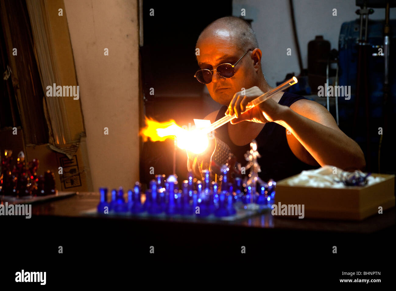 A craftsman in Mdina in Malta works on a glass chess set - Stock Image
