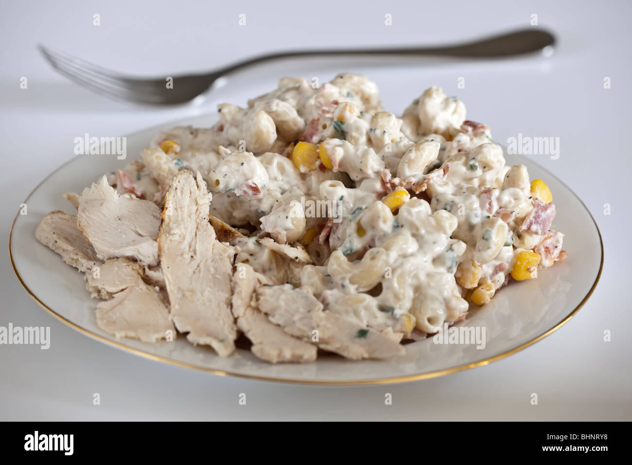 Chicken and bacon Pasta in a mayonnaise sauce on a white plate - Stock Image