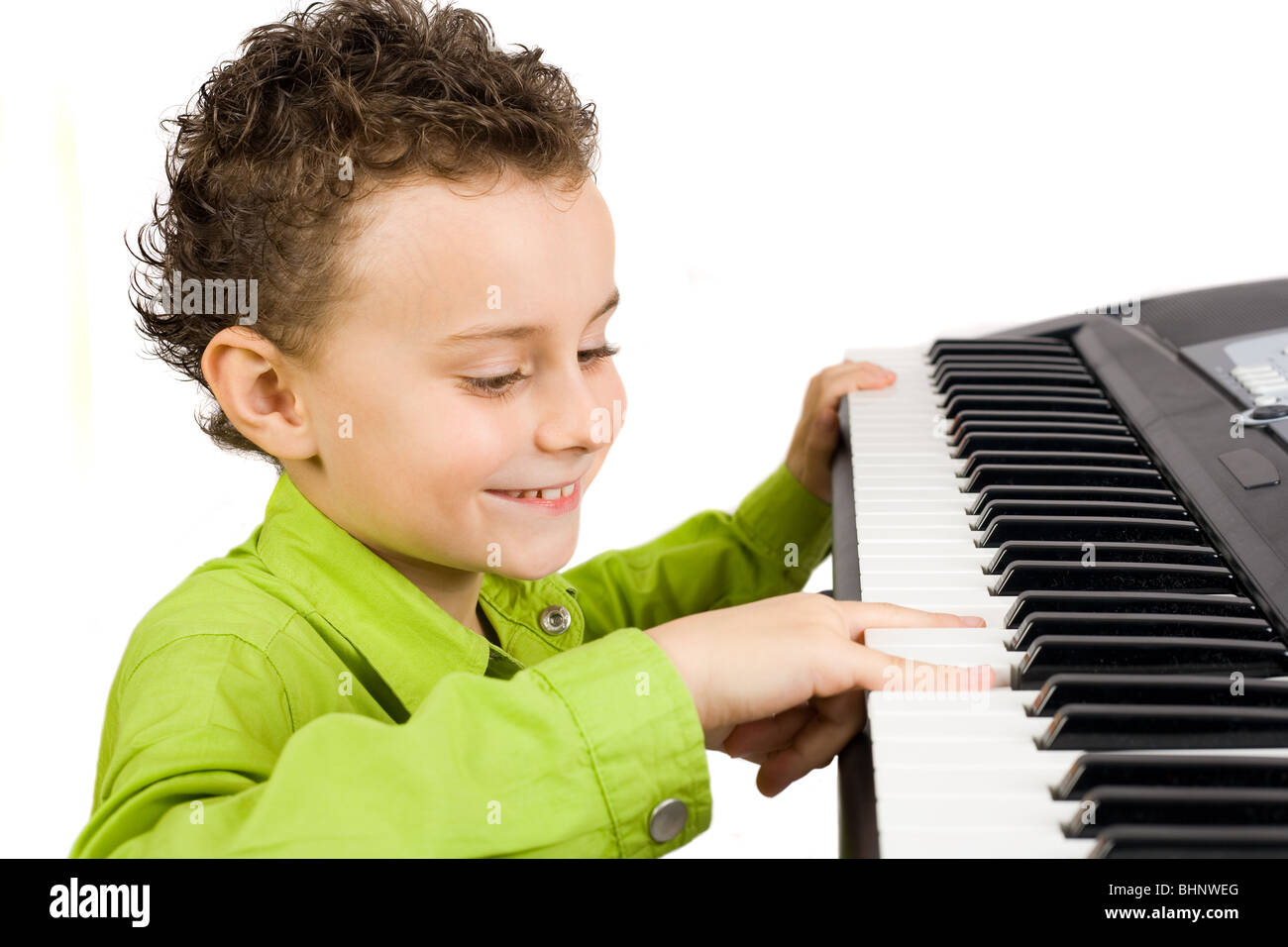 Cute little boy playing synthesizer or piano, isolated on white background - Stock Image