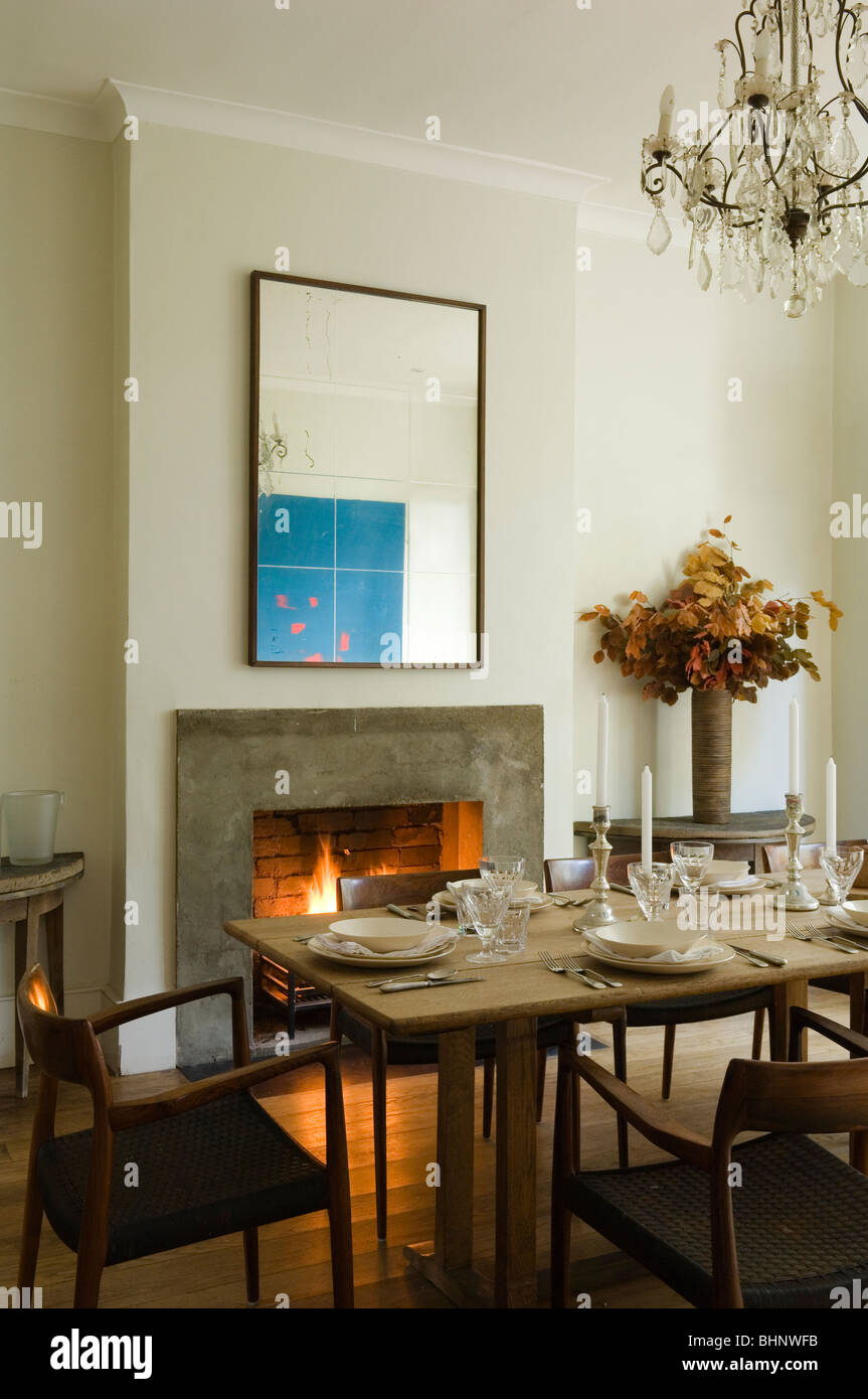Dining table with laid places by fireplace with Checkett artwork - Stock Image