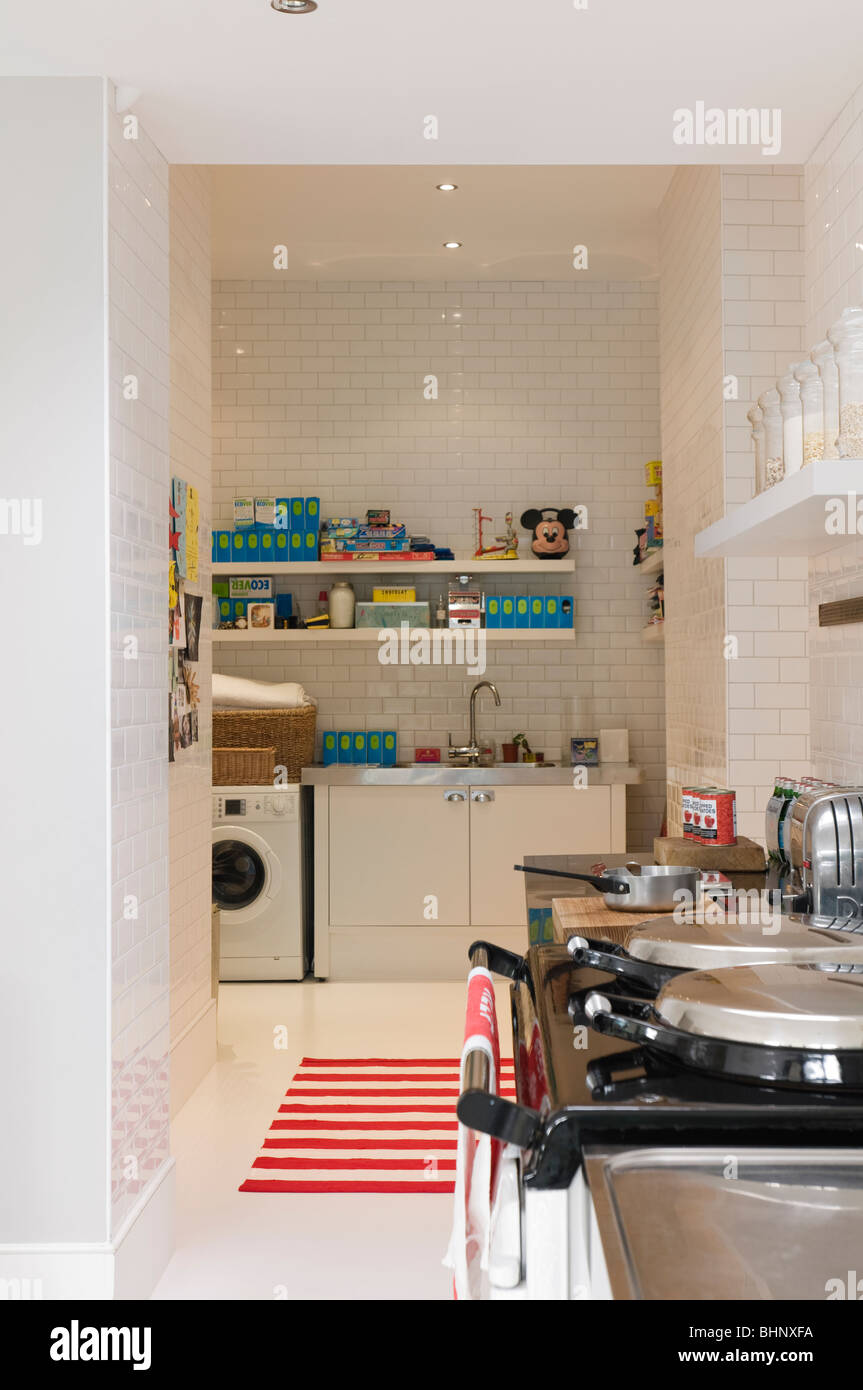 Running-bond tiled kitchen with aga and striped rug - Stock Image