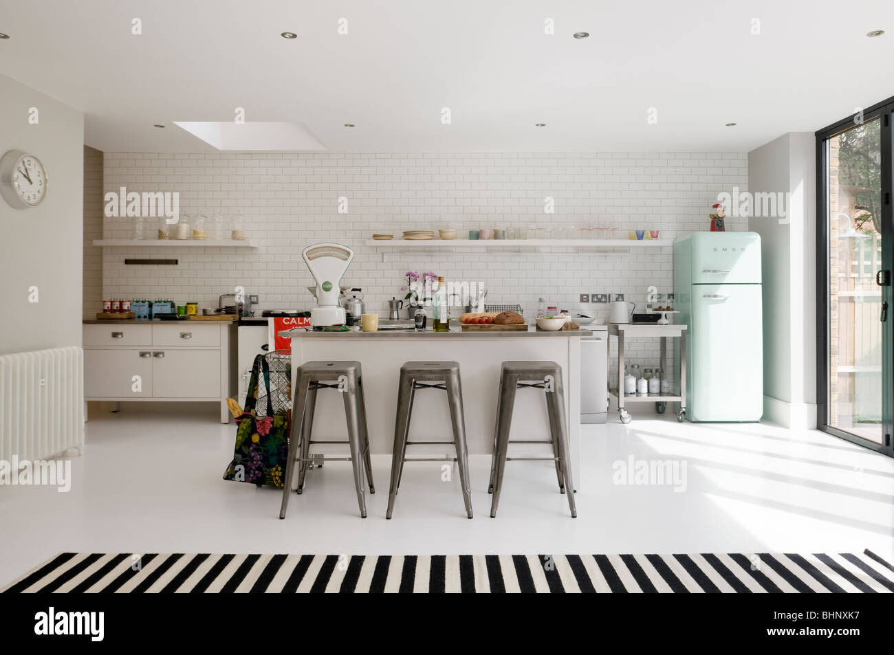 Open plan white-tiled kitchen with barstools and retro fridge - Stock Image