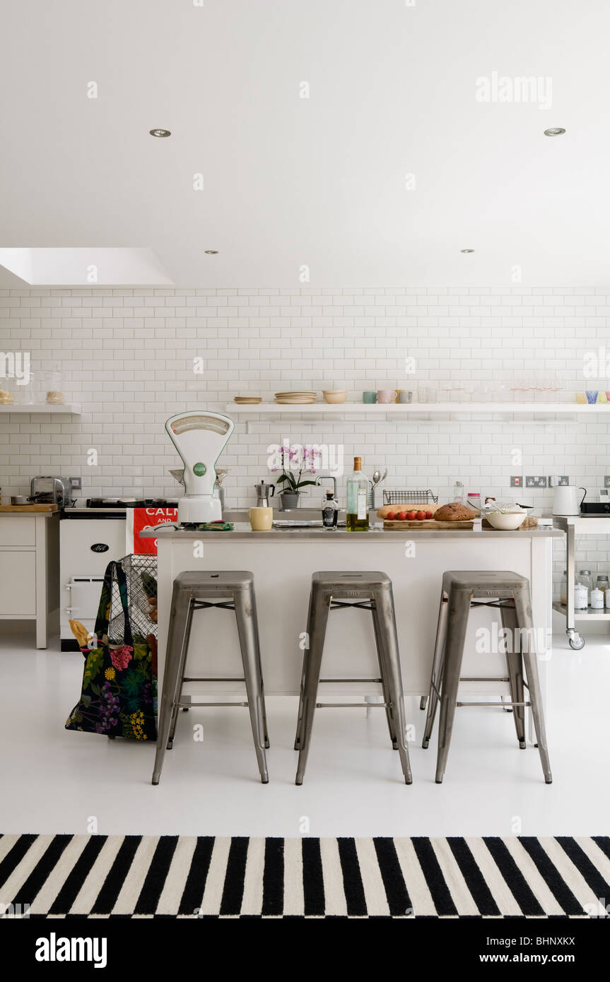 White tiled kitchen with barstools, striped runner rug and retro weighing scales - Stock Image