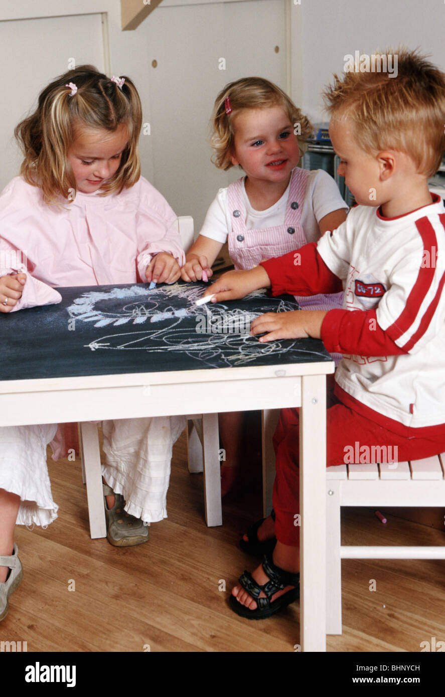 Children sharing blackboard and  chalk at school  due to groupswork - Stock Image