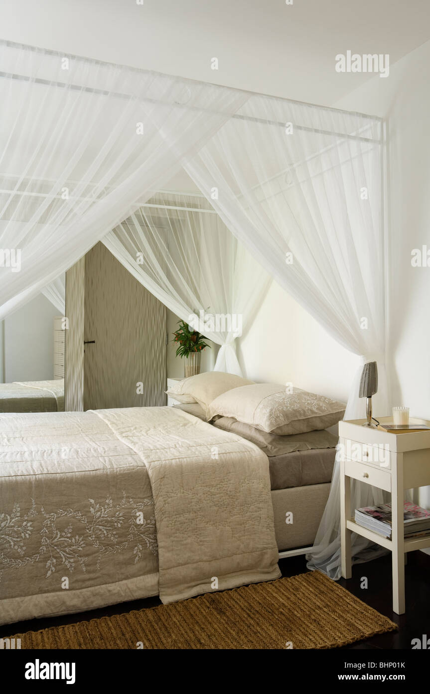 Fourposter bed with muslin curtains and beige quilt - Stock Image