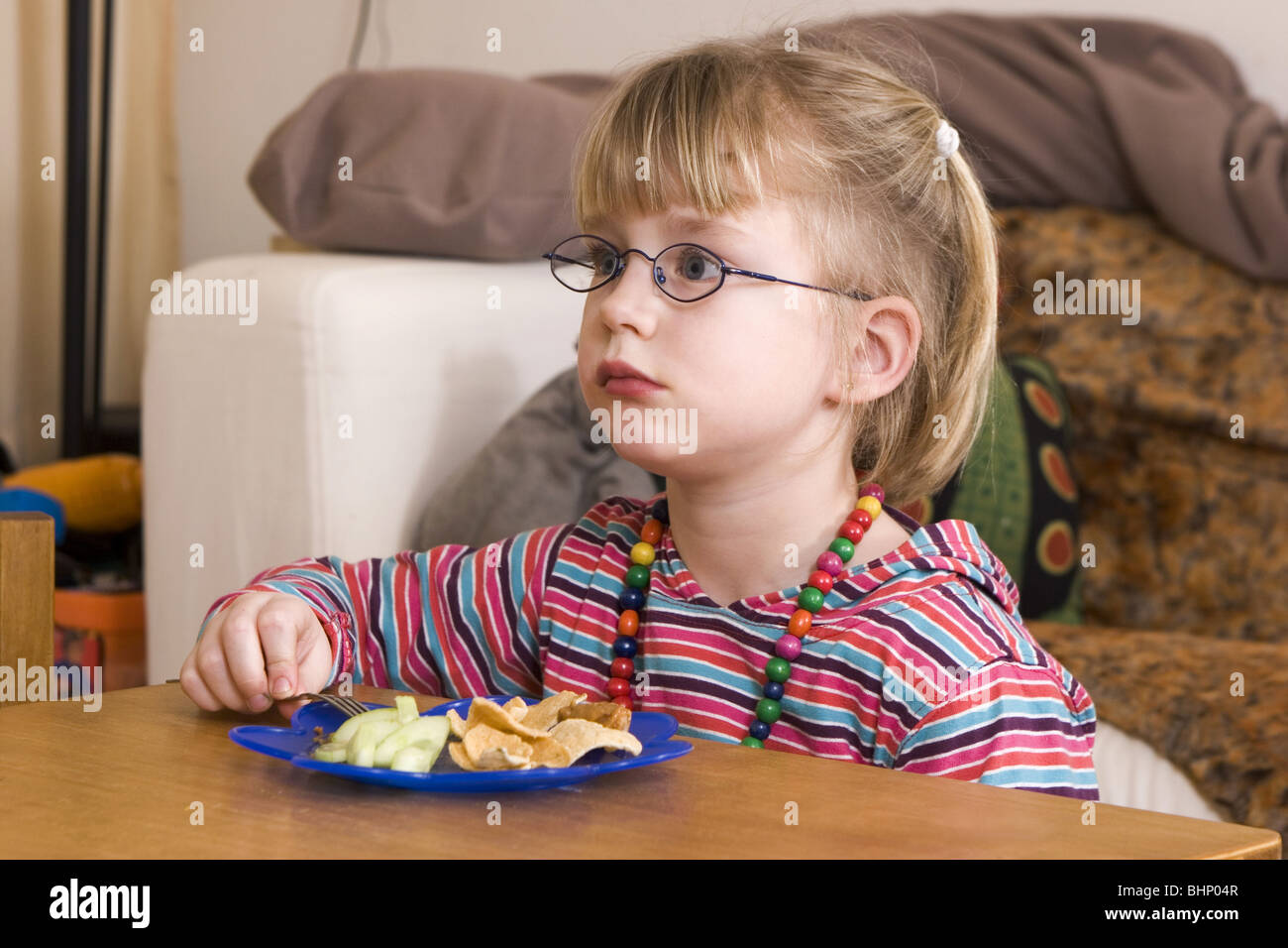 Young girl having family dinner alone while watching television and staring at the tv and eating her meal., shootcvs517003 - Stock Image