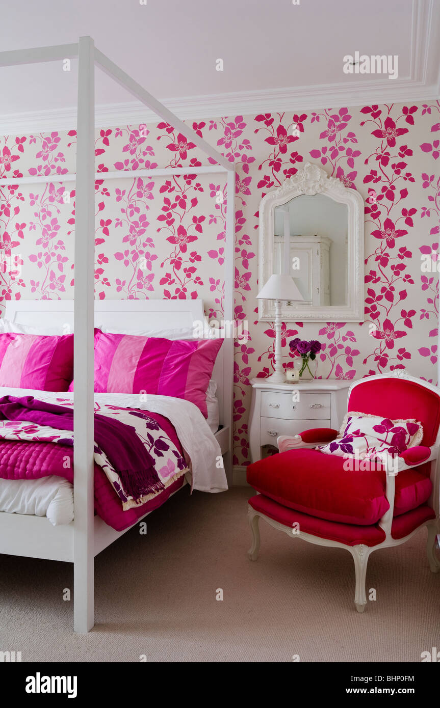 Bedroom with fourposter bed and patterned wallpaper - Stock Image