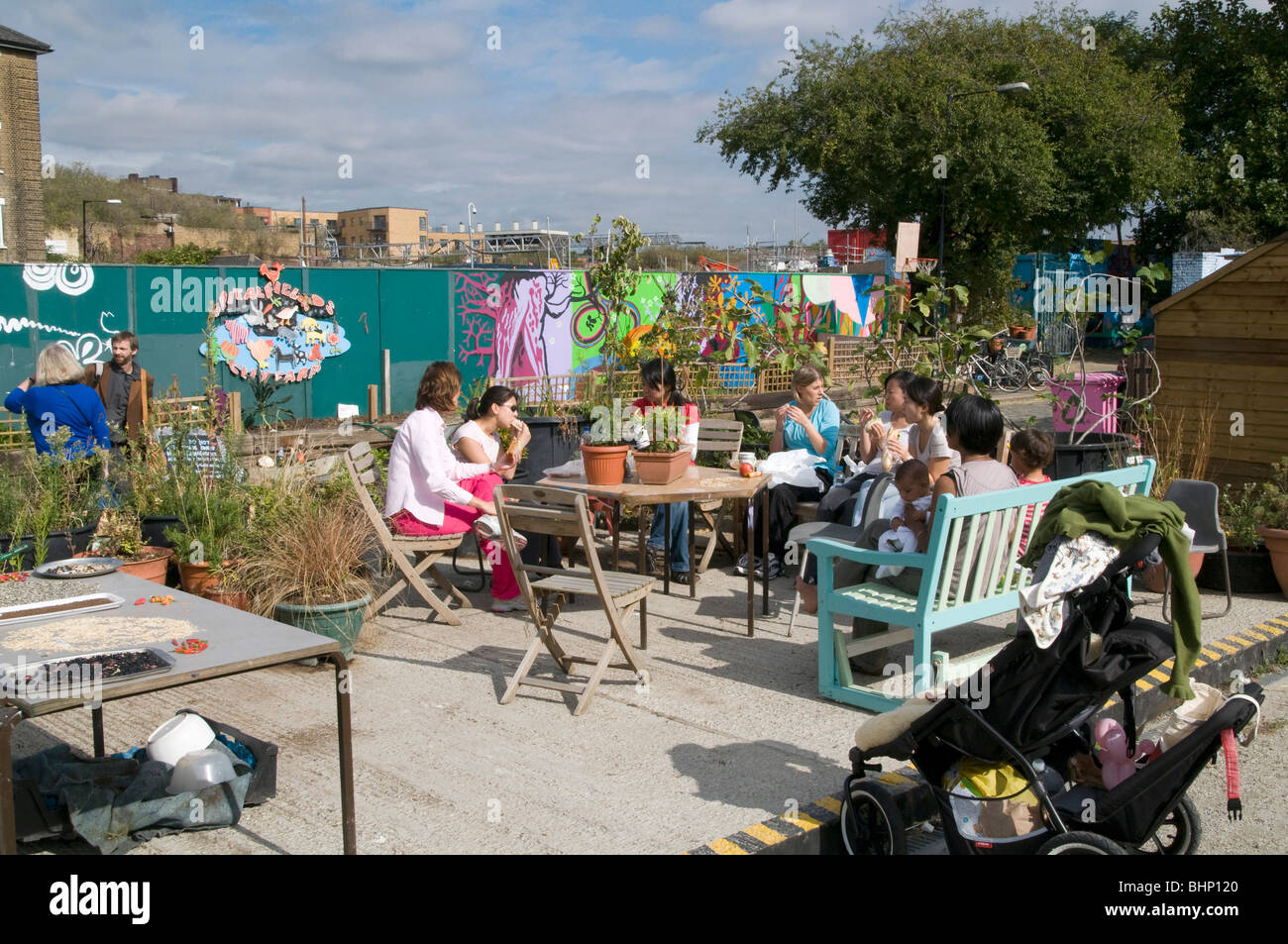 UK.Visiting volunteers and children by vegetable allotment at Spitalfields City Farm in east London - Stock Image