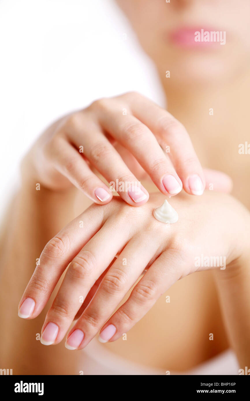 Young woman cares about her hands, applying cream on them. - Stock Image