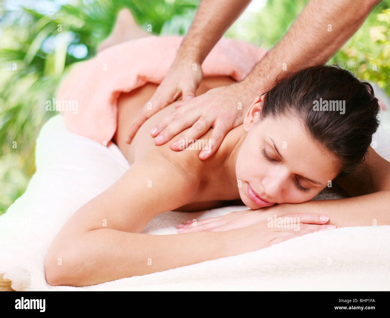 Young woman gets a massage. Eyes are closed. - Stock Image