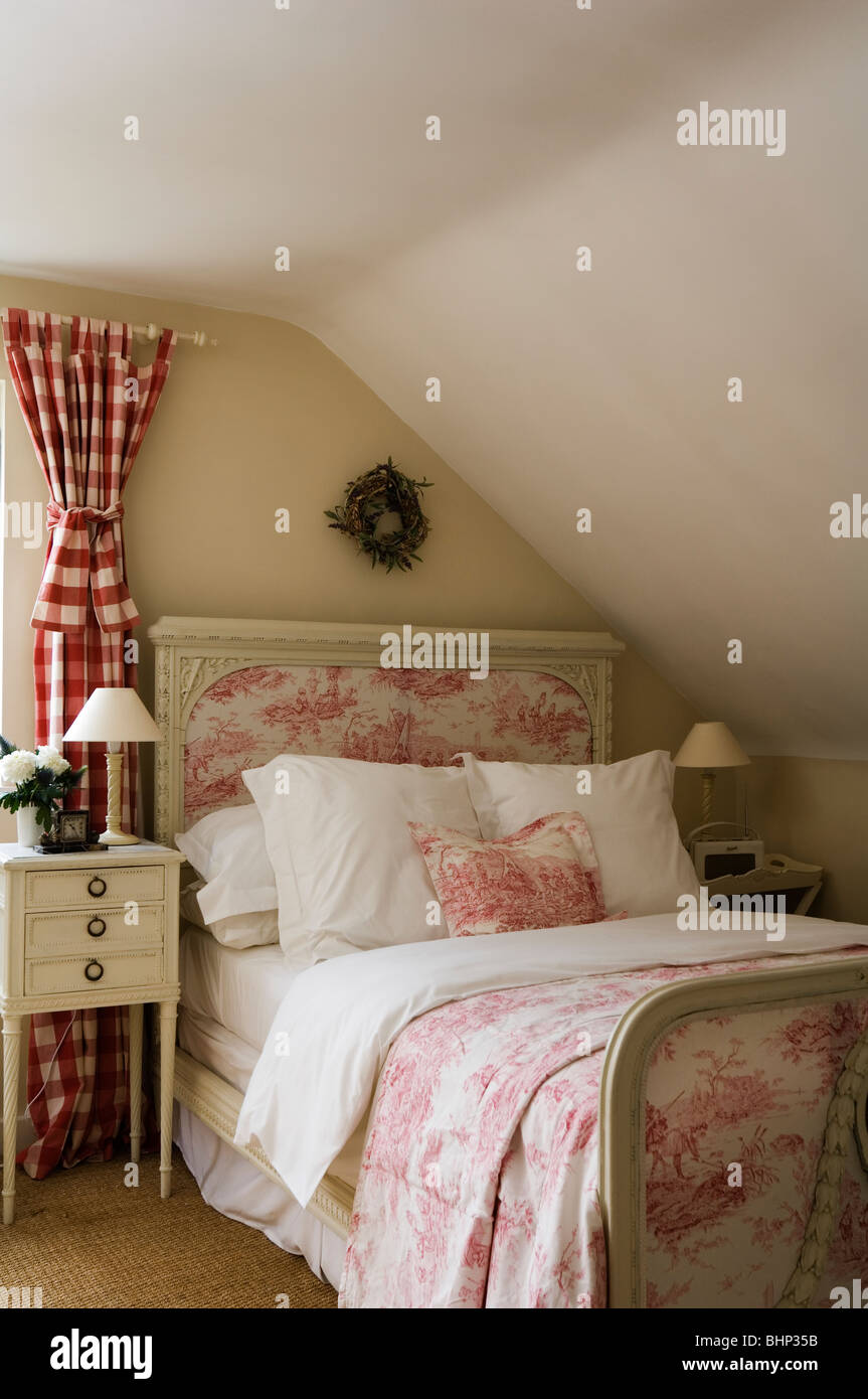 Cottage bedroom with bed in toile de jouy and checked curtains - Stock Image