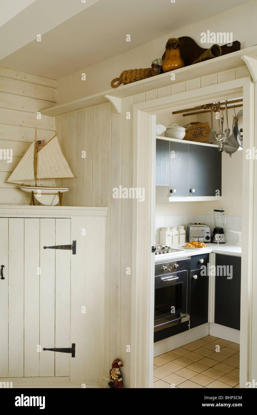 View through wood panelled doorway to kitchen - Stock Image