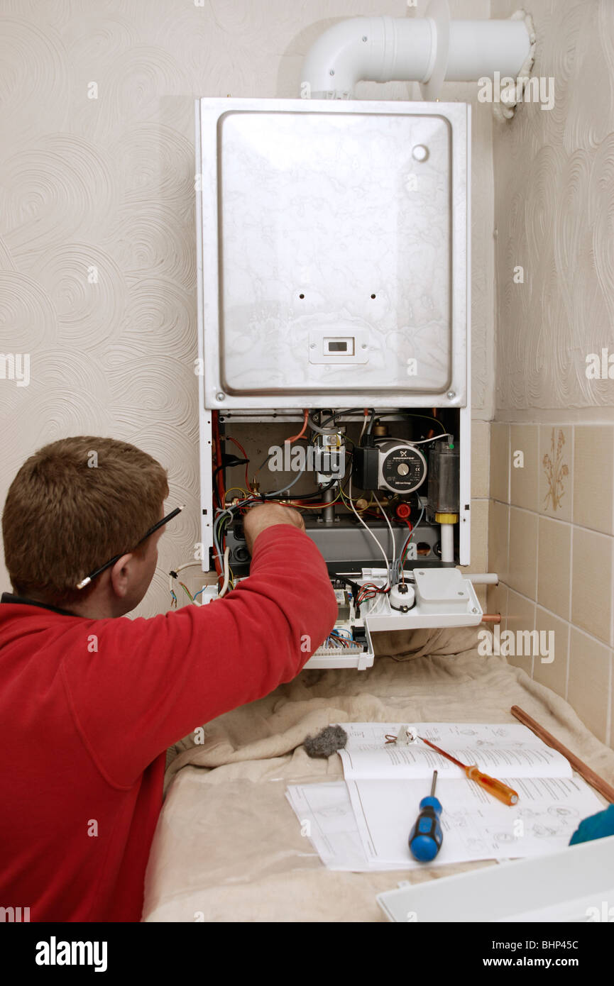 gas engineer / plumber installing an A rated condensing boiler with less emissions for the environment - Stock Image