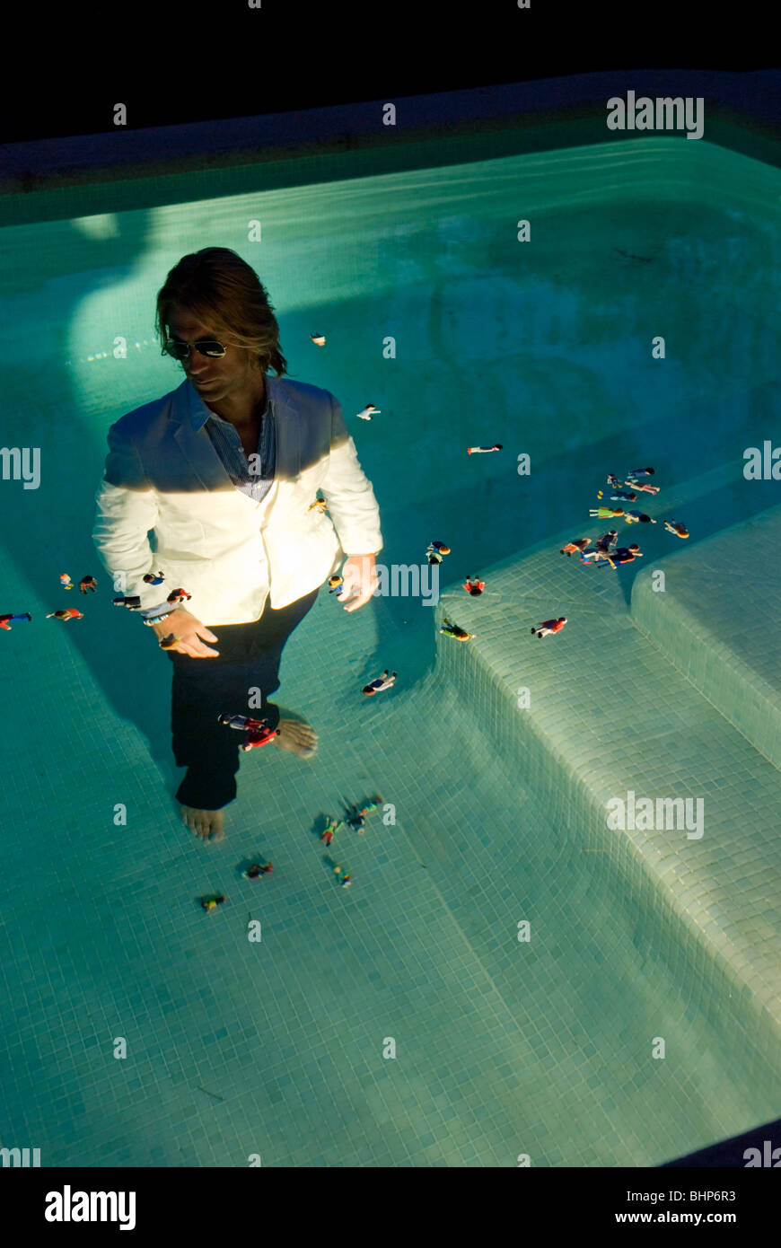 bizarre image of a suited blond man with sunglasses submerged in a  swimming pool surrounded by floating toy figure - Stock Image