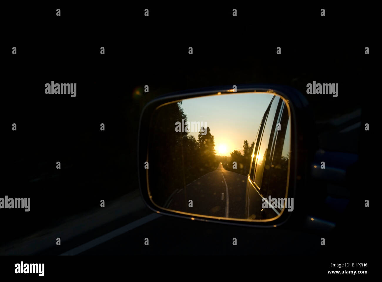 a rear wing mirror shows the view of landscape of passing road at sunset disappearing behind moving car - Stock Image