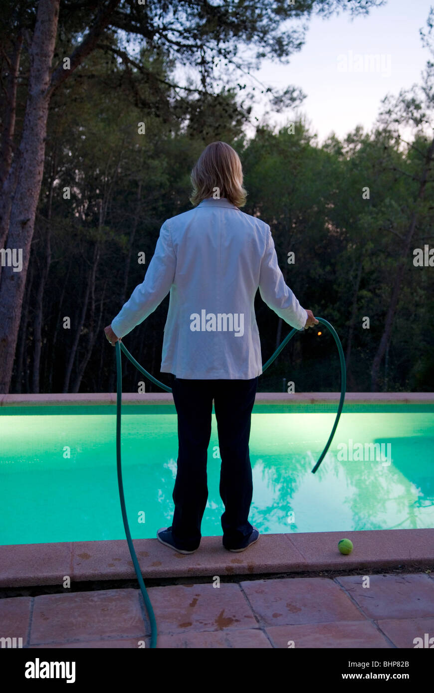 looking at the rear of a suited blond man standing by the side of swimming pool with a hose pipe in his hands - Stock Image