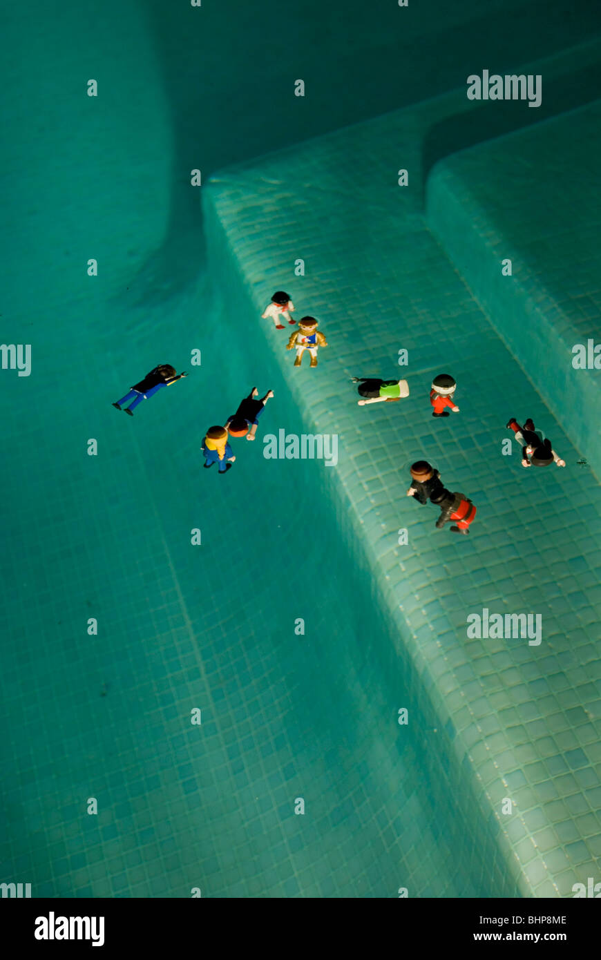 looking down at toy figures lit up floating in swimming pool at night - Stock Image
