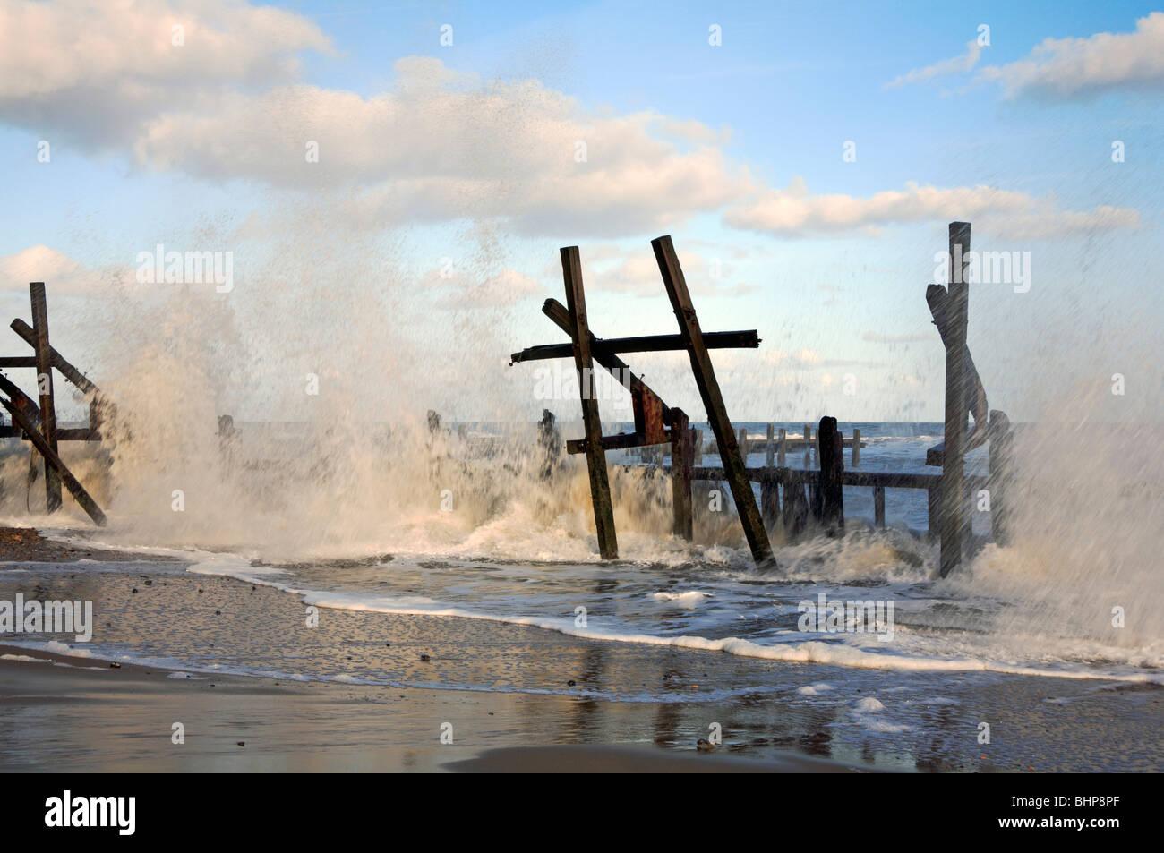 Waves pounding abandoned breakwaters at Happisburgh, Norfolk, United Kingdom. - Stock Image