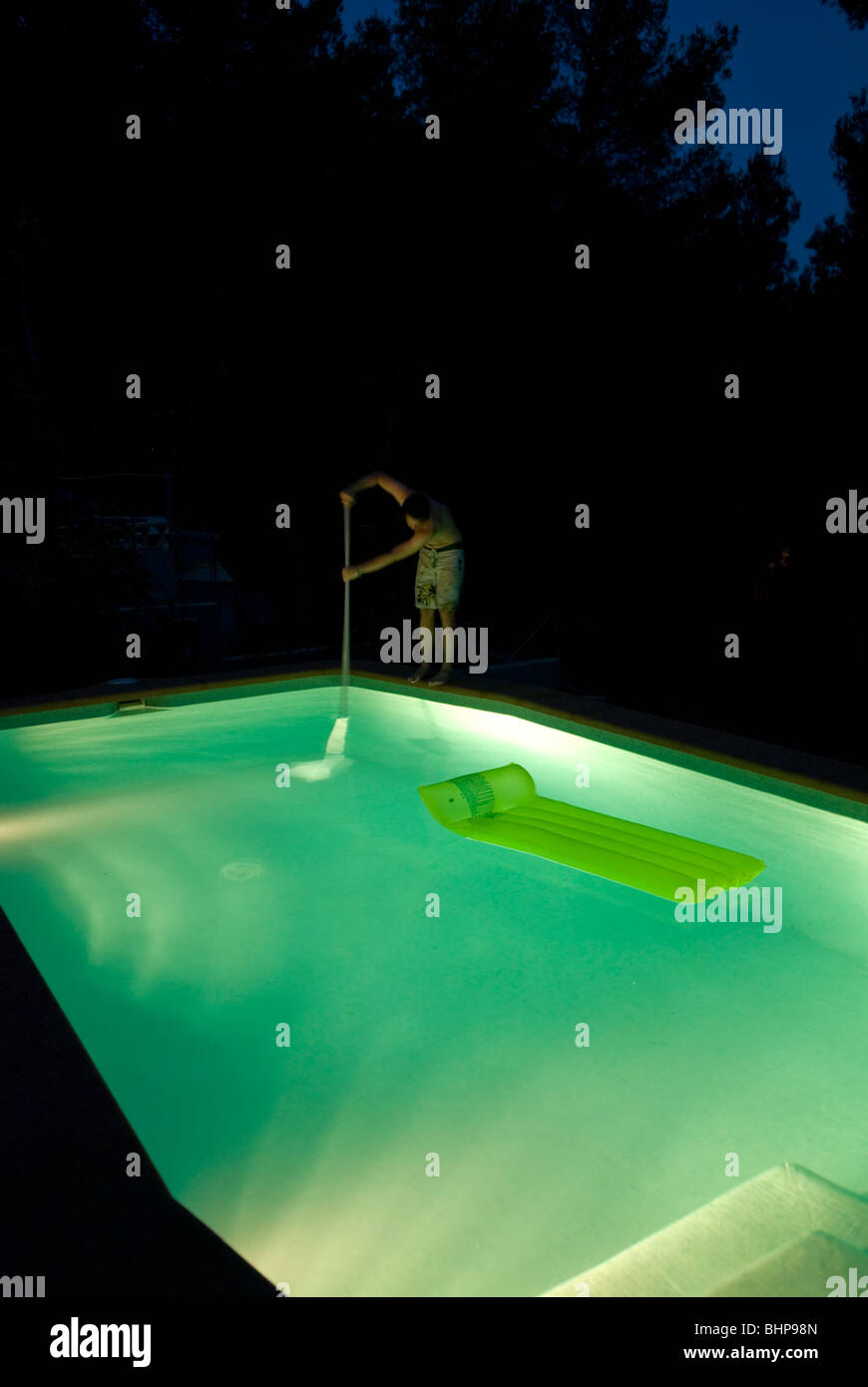 view of a lone man standing on the edge of a light up pool at night cleaning it with a net Stock Photo
