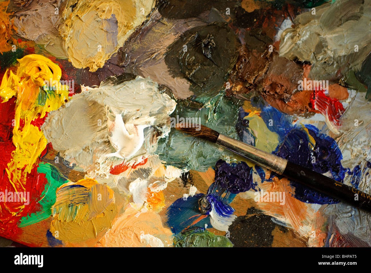paint brush and oil paints pigments on artist's palette - Stock Image