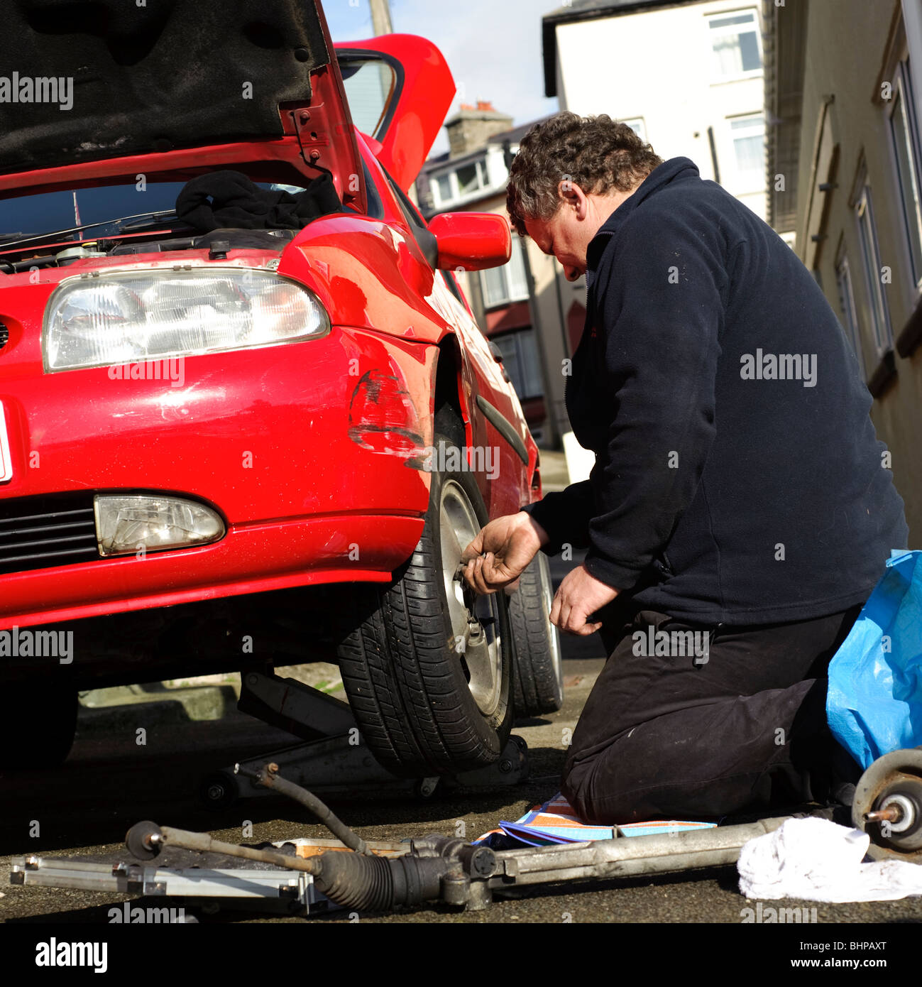 Man fixing wheel on a red car, UK - repairing wheel changing tyre - Stock Image