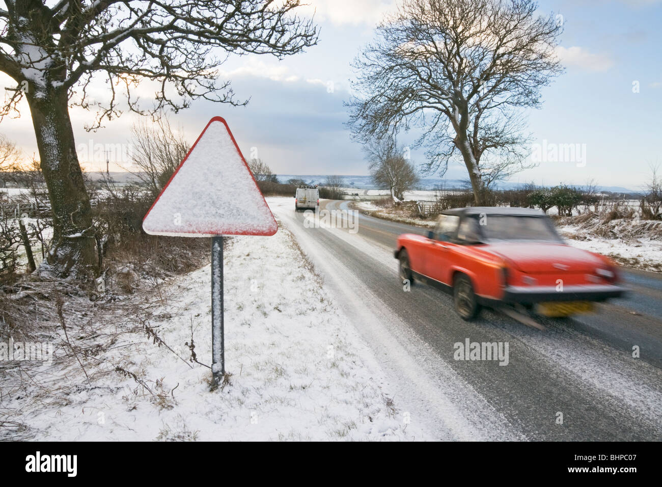 Road warning sign covered with snow alongside a slush covered road, North Yorkshire, UK - Stock Image