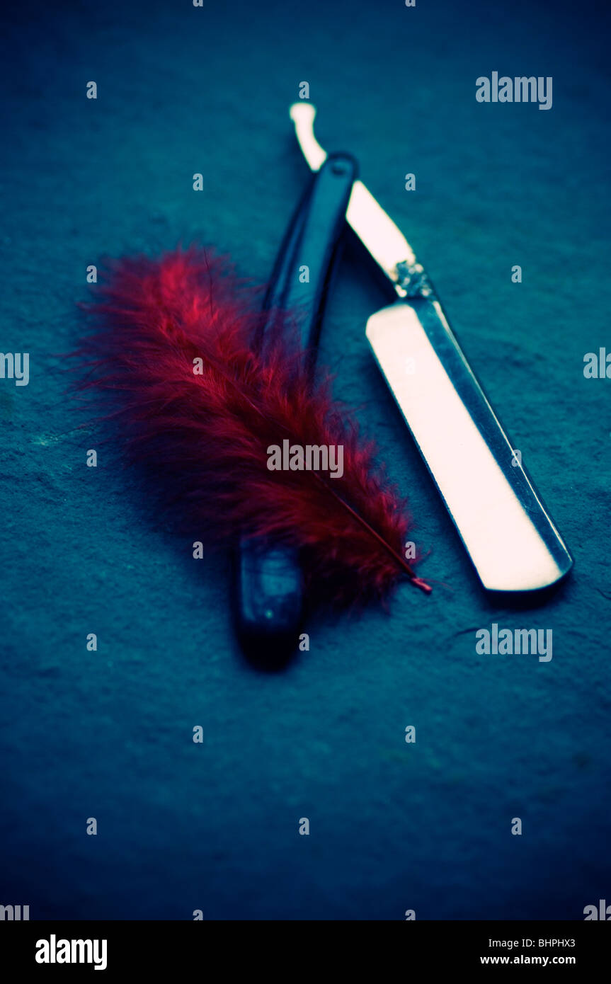 Red feather next to a cutthroat razor - Stock Image