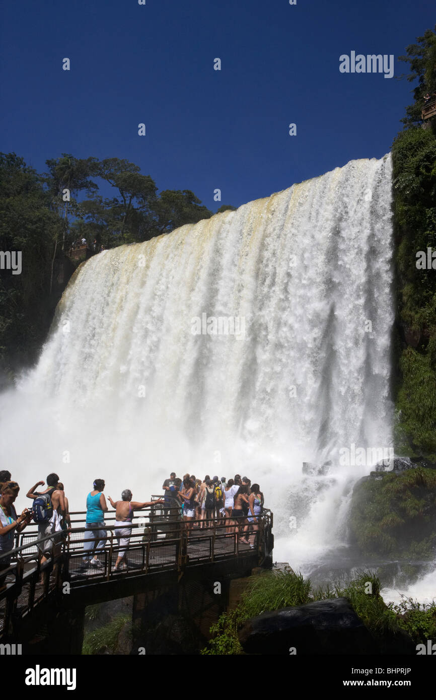 tourists at viewpoint underneath the adan y eva adam and eve fall on the lower circuit in iguazu national park - Stock Image