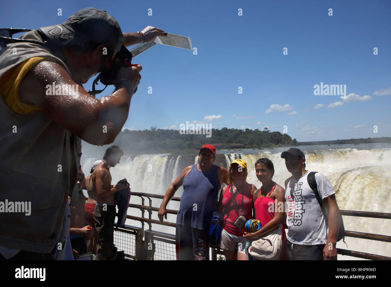 tour group posing for photos on the walkway above the devils throat garganta del diablo iguazu national park argentina - Stock Image