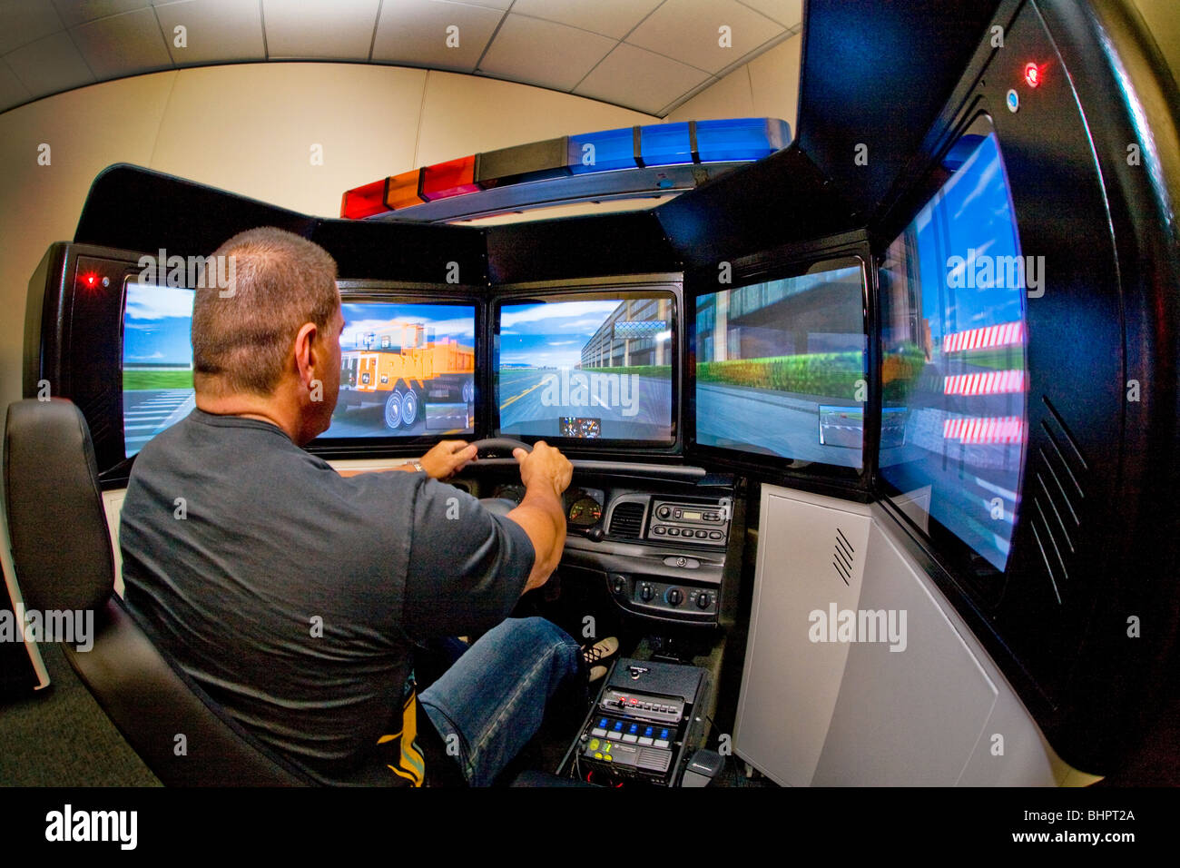 A police officer practices high speed driving skills in a patrol car simulator with a real steering wheel and seat. - Stock Image