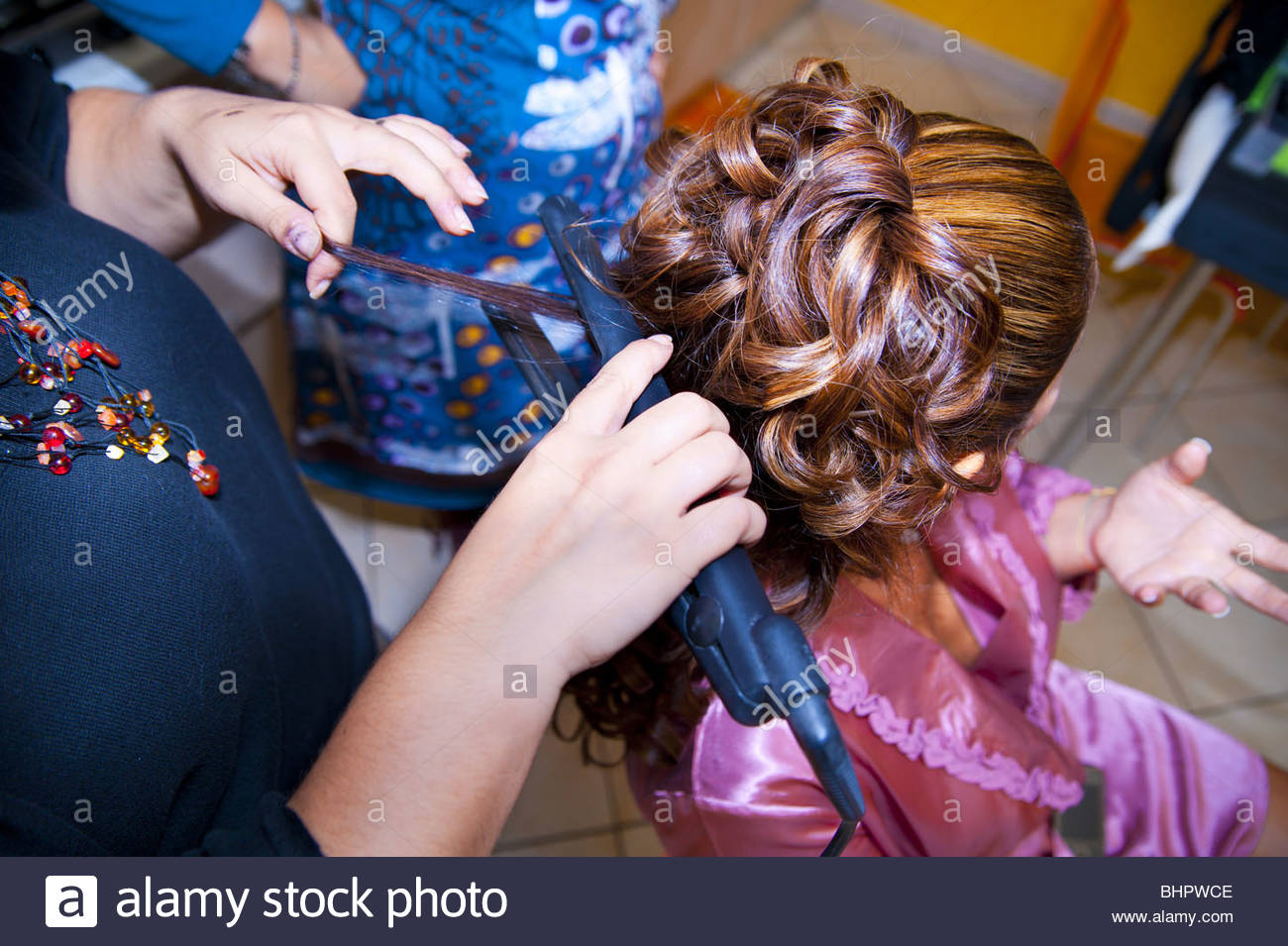 hairdresser applying a straight iron on a woman hairdo - Stock Image