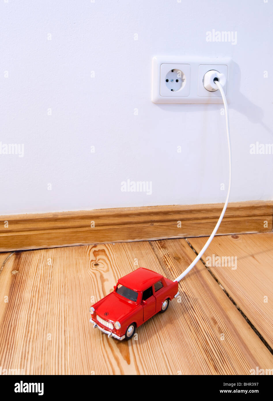 Concept of toy electric car being recharged by plug-in connection to electric supply in the home - Stock Image
