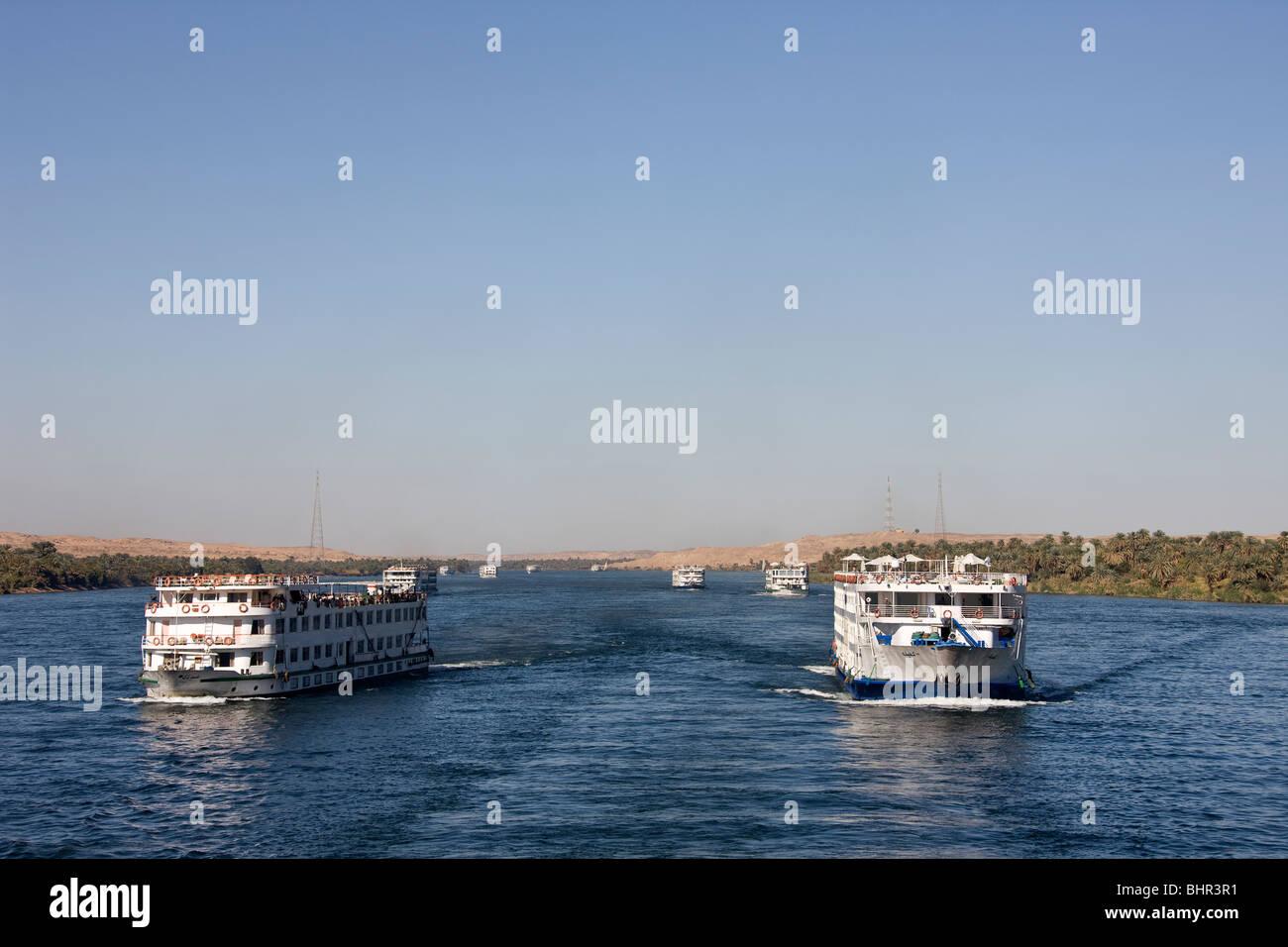 Holiday cruise ships traveling up the River Nile towards Esna Lock. - Stock Image
