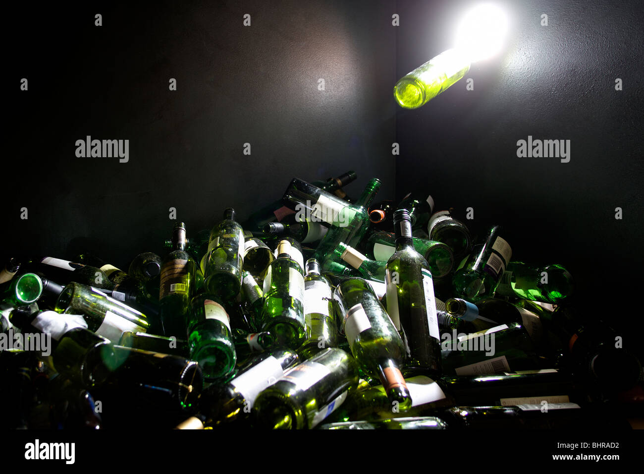 A glass bottle being pushed into a glass recycling bin - Stock Image