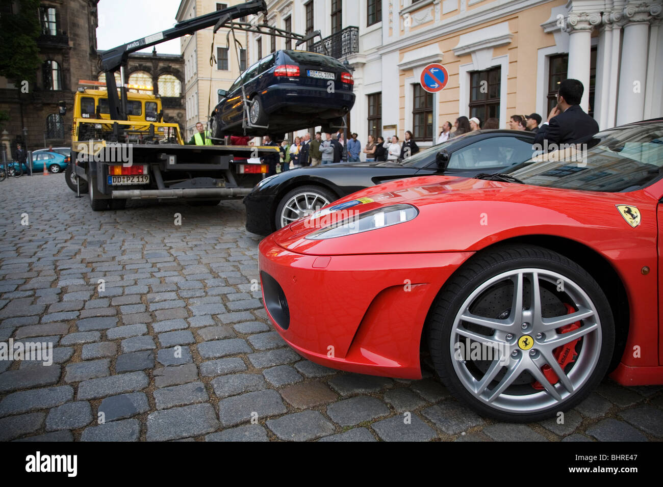 Ferrari in front of a car removal. Dresden, Germany - Stock Image