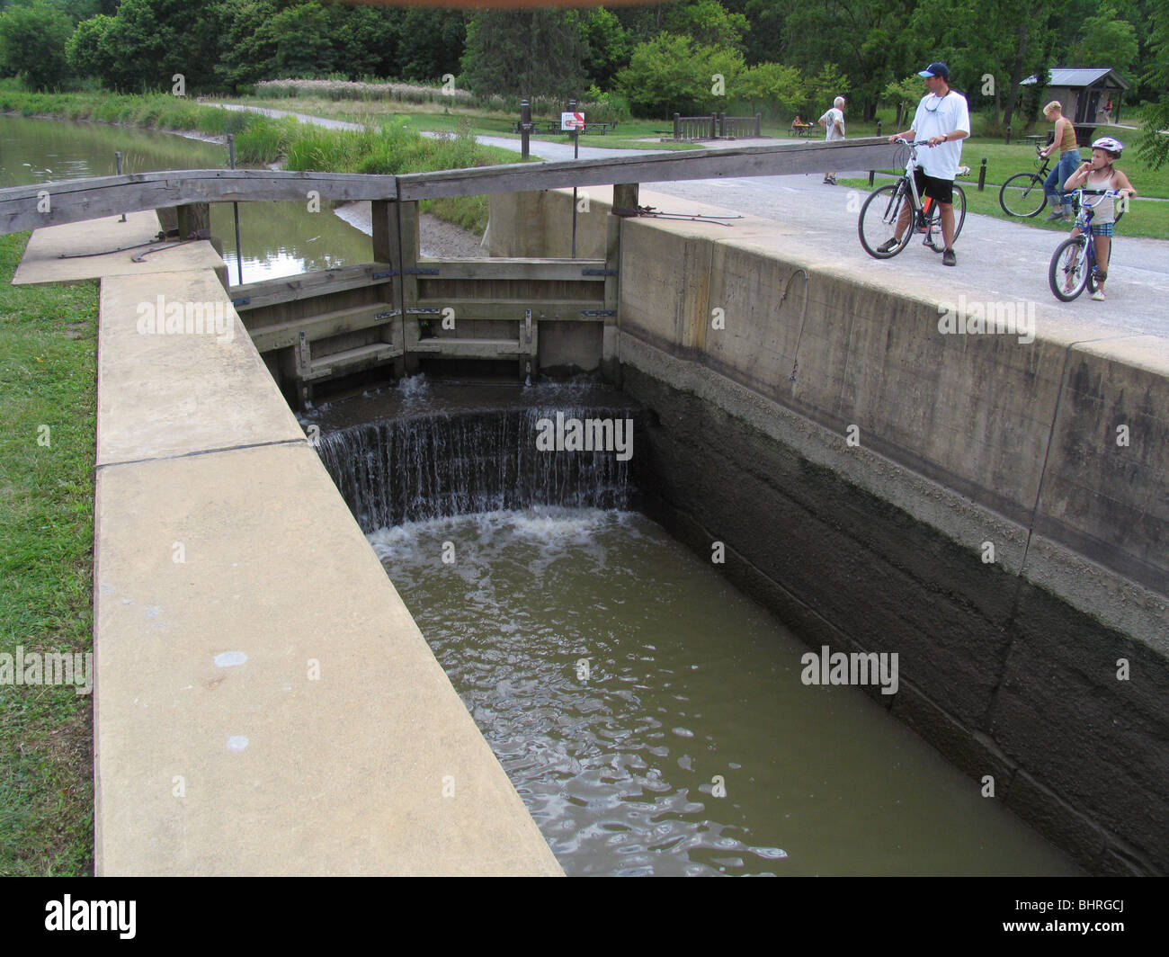 Canal lock Ohio and Erie Canal Towpath Trail bikers Cuyahoga Valley National Park Ohio - Stock Image