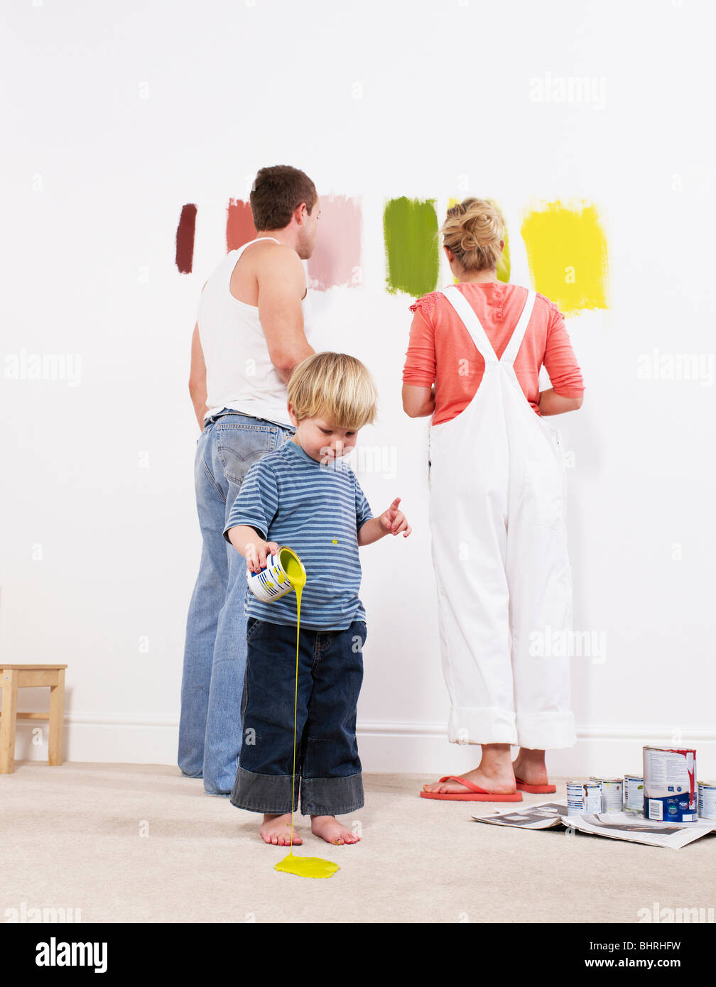 Toddler boy pouring paint on carpet - Stock Image