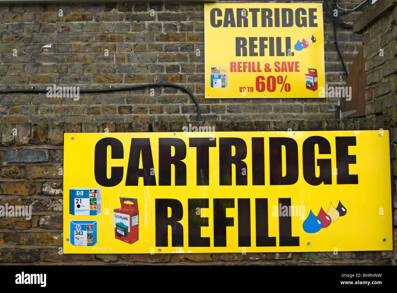 bright street adverts on a brick wall for cartridge refill, in kingston upon thames, surrey, england - Stock Image