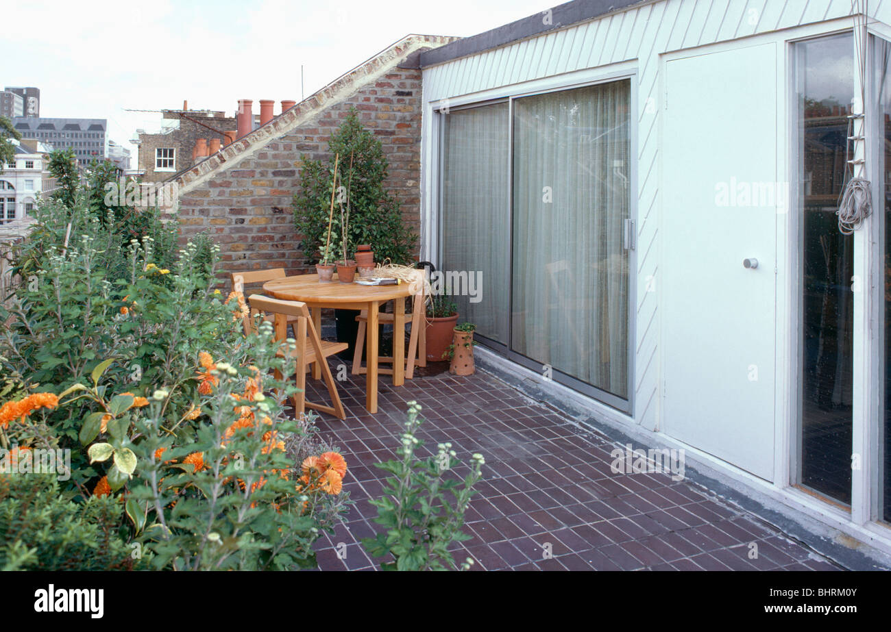 Wooden Table And Chairs On Paved Roof Garden Of Small Loft Conversion With  Patio Doors