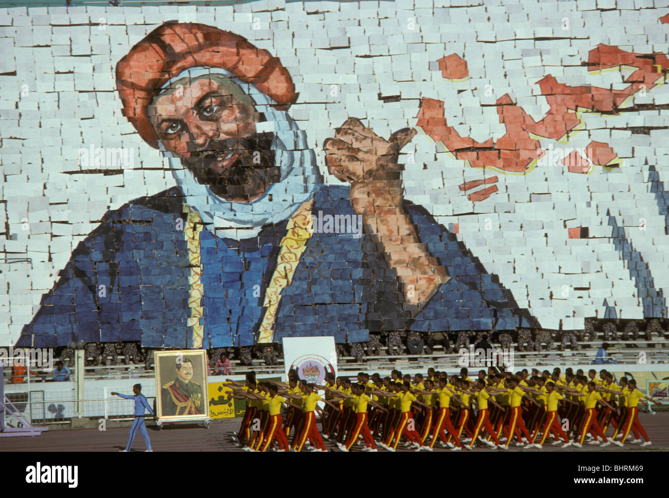 Contestants at the Police Games in Baghdad Stadium walk past a giant card tableau in Baghdad Iraq in 1978 - Stock Image