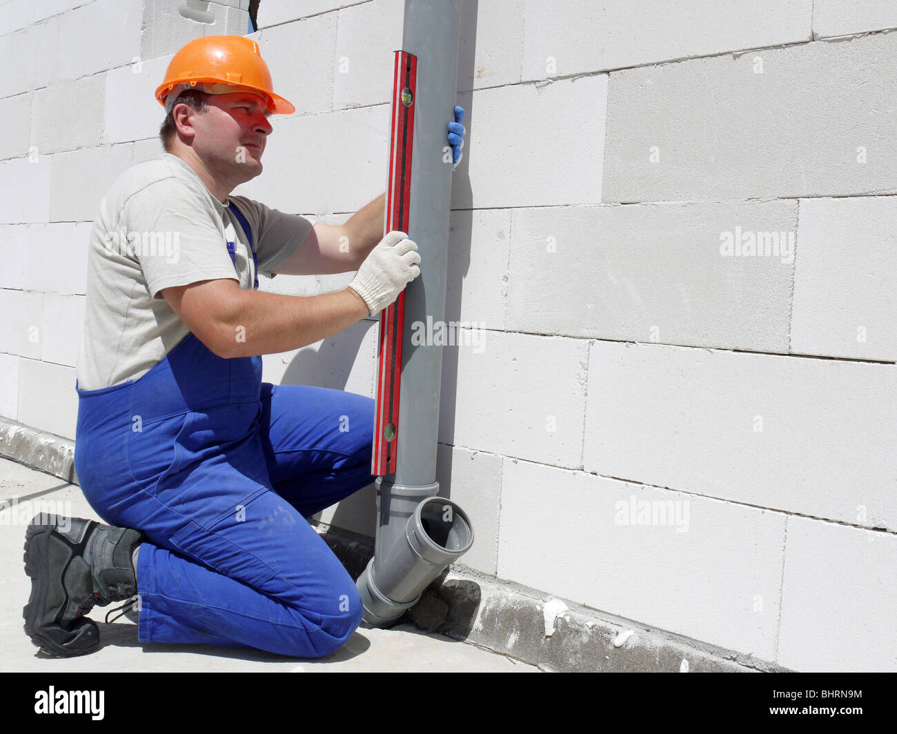 Plumber Using Level For Checking Plumb Line Of Assembled Pvc Sewage
